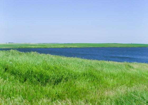 Rolling green prairie grasses next to beautiful blue lake